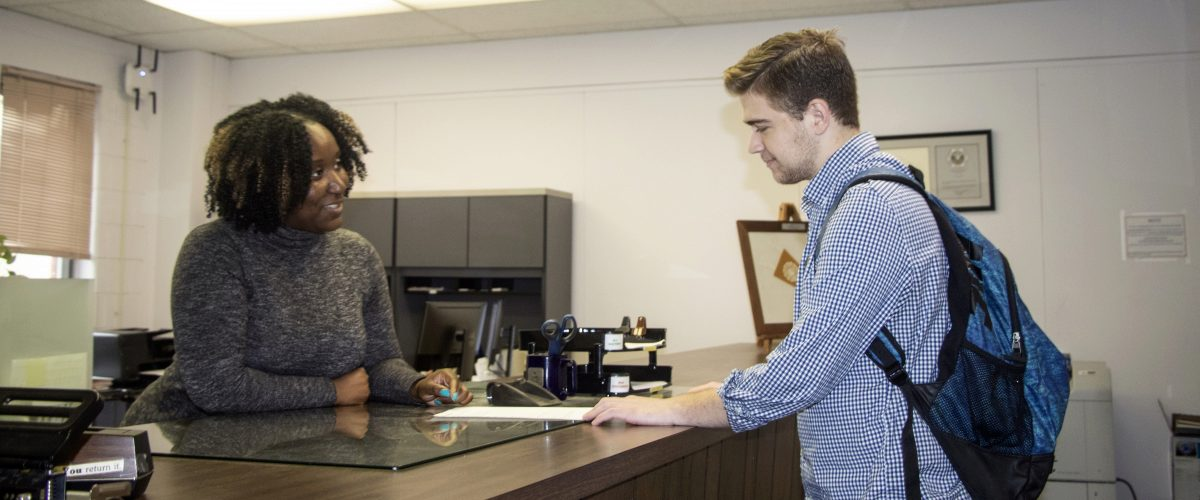 Kamaria Richards helping a student at the front desk of the Academic Office