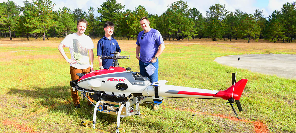 Three grad students standing behind an unmanned rotorcraft in a field