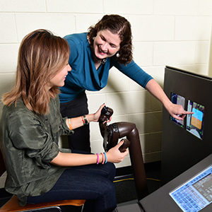 Dr. Feigh with a student using the Reconfigurable Flight Simulator.
