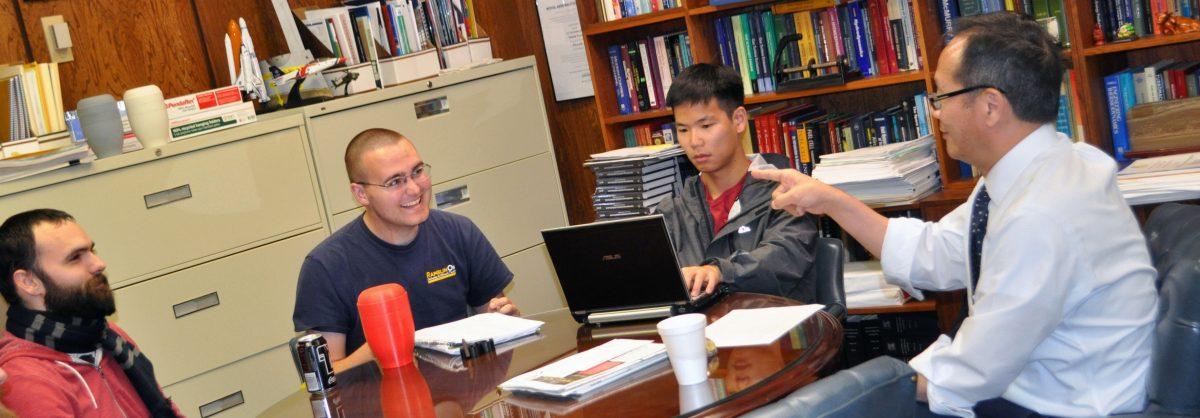 Professor and 3 MSAE students having a discussion at a table.